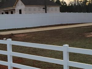 8 ft tall privacy fence in back with white ranch rail in front, both vinyl